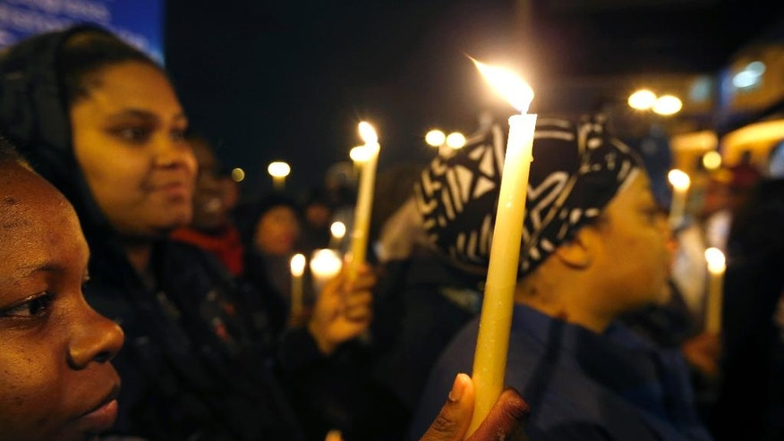 Kaneisha Tiller, far left, and Crystal Hamilton, hold candles during a vigil to honor former mayor and current DC City Council member Marion Barry, Sunday, Nov. 23, 2014, in Washington. Barry, who staged a comeback after a 1990 crack cocaine arrest, died early Sunday, Nov. 23, 2014. He was 78. (AP Photo/Alex Brandon)