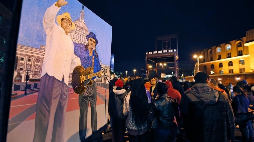 Oliver Johnson, Jr., holds an acrylic painting he did of former Mayor Marion Barry and Chuck Brown, during a vigil to honor former Mayor and current DC City Council member Marion Barry, Sunday, Nov. 23, 2014, in Washington. Barry, who staged a comeback after a 1990 crack cocaine arrest, died early Sunday morning Nov. 23, 2014. He was 78. (AP Photo/Alex Brandon)