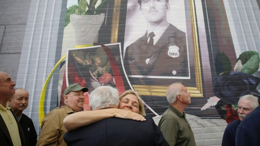 Maureen Faulkner, widow of slain Philadelphia police officer Daniel Faulkner, embraces Joe McGill who prosecuted Mumia Abu-Jamal for the murder of her husband, underneath a new mural of him, Monday, Nov. 24, 2014, in Philadelphia. The mural is painted on the side of the police station Faulkner worked at in the Chinatown section of the city. Daniel Faulkner was shot to death by Mumia Abu-Jamal on a downtown street in 1981. (AP Photo/Matt Rourke)