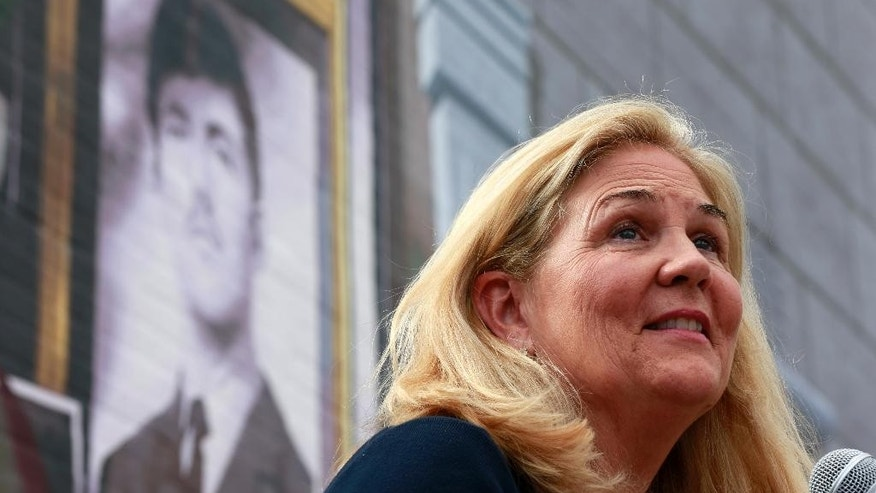 Maureen Faulkner, widow of slain Philadelphia police officer Daniel Faulkner, speaks beneath a new mural of him Monday, Nov. 24, 2014, in Philadelphia. The mural is painted on the side of the police station Faulkner worked at in the Chinatown section of the city. Daniel Faulkner was shot to death by Mumia Abu-Jamal on a downtown street in 1981. (AP Photo/Matt Rourke)