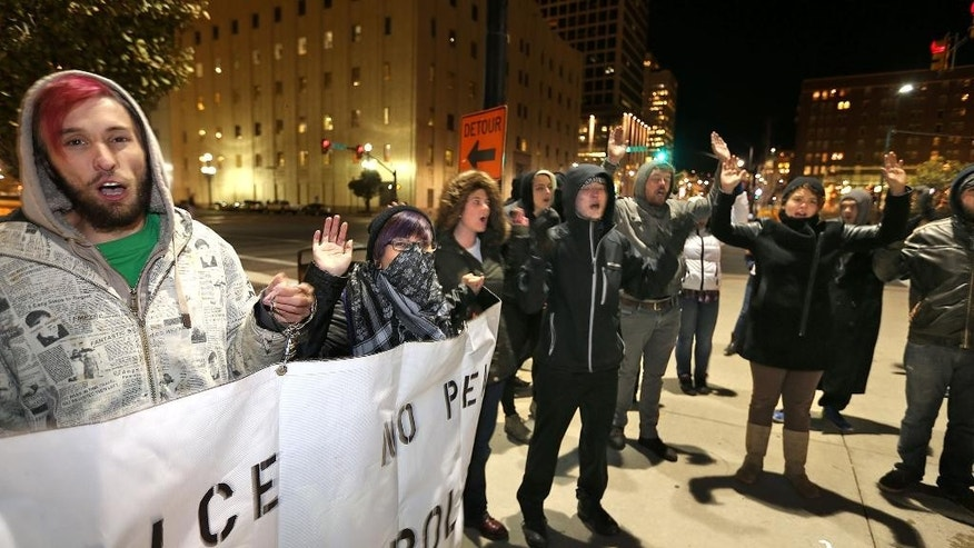 People protest outside the Wallace F Bennett Federal Building on the grand jury has decision not to indict Ferguson police officer Darren Wilson in the death of Michael Brown Monday, Nov. 24, 2014, in downtown Salt Lake City.  (AP Photo/The Deseret News, Tom Smart)