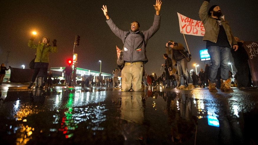 Anthony Grimes kneels on a rain-soaked street as he blocks traffic with other protesters Sunday, Nov. 23, 2014, in St. Louis. Ferguson and the St. Louis region are on edge in anticipation of the announcement by a grand jury whether to criminally charge officer Darren Wilson in the killing of 18-year-old Michael Brown. (AP Photo/David Goldman)