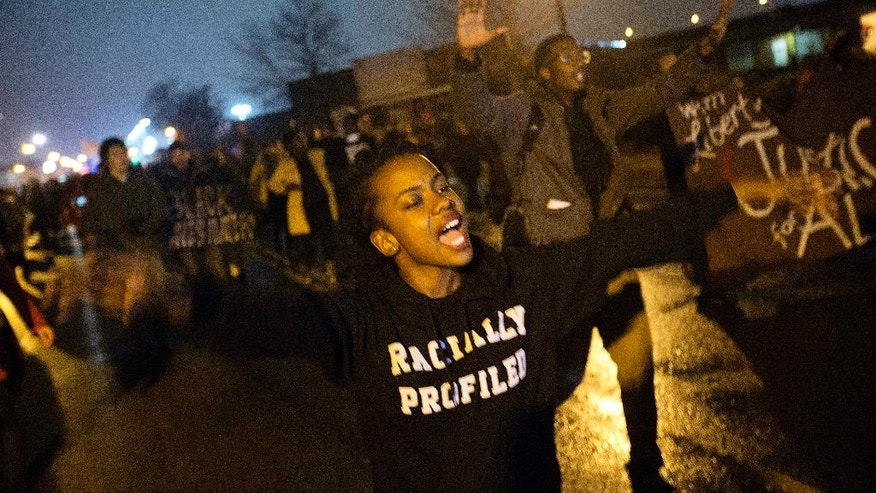"Brittany Ferrell, of St. Louis, chants ""hands up don't shoot"" while marching through the streets protesting the August shooting of Michael Brown, Sunday, Nov. 23, 2014, in St. Louis. Ferguson and the St. Louis region are on edge in anticipation of the announcement by a grand jury whether to criminally charge officer Darren Wilson in the killing of 18-year-old Brown. (AP Photo/David Goldman)"
