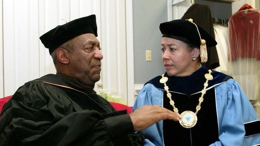 FILE - In this May 14, 2006 file photo, keynote speaker Bill Cosby, left, and Spelman College President Dr. Beverly Tatum talk before the start of commencement at the school in Atlanta. Cosby's legacy of giving is decades-old and extensive, topped by a $20 million gift to Spelman College in 1988 and including, among many other donations, $3 million to the Morehouse School of Medicine; $1 million in 2004 to the U.S. National Slavery Museum in Fredericksburg, Virginia; and $2 million from Cosby's wife, Camille, to St. Frances Academy in Baltimore in 2005. (AP Photo/W.A. Harewood, File)