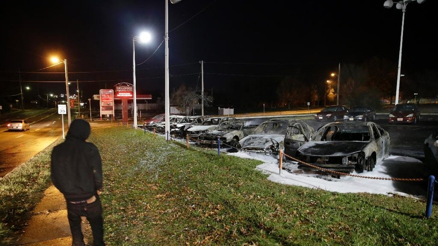 A pedestrian passes by damaged cars in a used car dealership Tuesday, Nov. 25, 2014, in Dellwood, Mo. A grand jury has decided not to indict Ferguson police officer Darren Wilson in the death of Michael Brown, the unarmed, black 18-year-old whose fatal shooting sparked sometimes violent protests. (AP Photo/David Goldman)