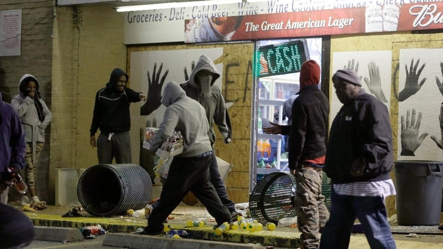 Ferguson Market and Liquor store is vandalized after the announcement of the grand jury decision Monday, Nov. 24, 2014, in Ferguson, Mo. A grand jury has decided not to indict Ferguson police officer Darren Wilson in the death of Michael Brown, the unarmed, black 18-year-old whose fatal shooting sparked sometimes violent protests. (AP Photo/Jeff Roberson)