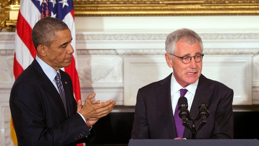President Barack Obama, left, applaudes Defense Secretary Chuck Hagel, right, in the State Dining Room of the White House in Washington, Monday, Nov. 24, 2014. Hagel is stepping down under pressure from Obama's Cabinet, senior administration officials said Monday, following a tenure in which he has struggled to break through the White House's insular foreign policy team. (AP Photo/Pablo Martinez Monsivais)