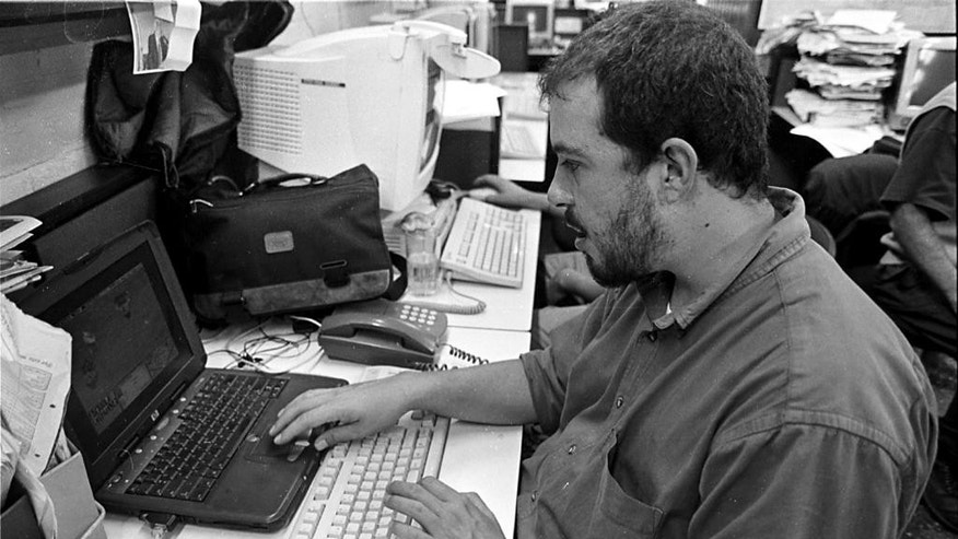 In this Sept. 2003 photo, Juan Carlos Llorca writes in the newsroom of El Periodico de Guatemala in Guatemala City. Llorca, El Paso correspondent for The Associated Press and a veteran reporter in his native Guatemala, has died. Llorca collapsed at his home in El Paso on Monday, Nov. 24, 2014, and was rushed to a local hospital, where he was pronounced dead, according to his sister, Maria Jimena Llorca. A cause of death was pending. He was 40. (AP Photo/Moises Castillo)