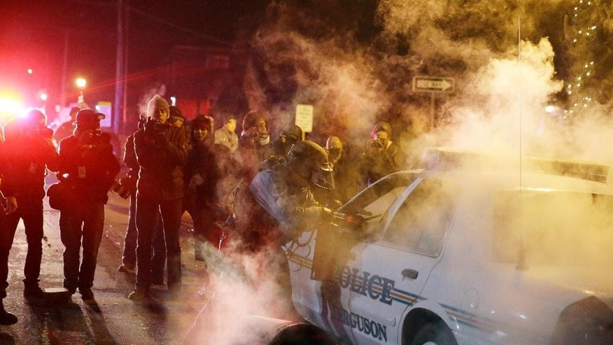 Nov. 25, 2014: A police officer approach a police vehicle after a protester has thrown a smoke device from the crowd in Ferguson, Mo. (AP/David Goldman)