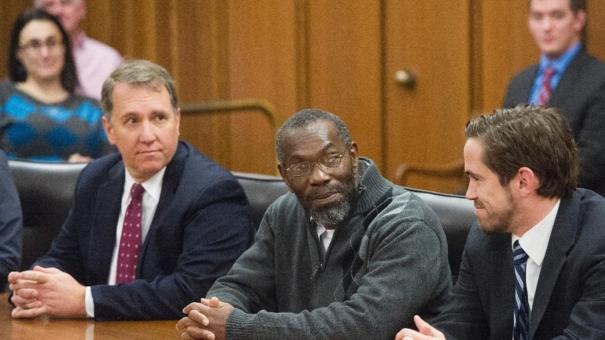 Ricky Jackson, 57, of Cleveland, center, with lawyers Mark Godsey, left, and Brian Howe, listens to Cuyahoga County Common Pleas Judge Richard McMonagle release Jackson from his life sentence, Friday, Nov. 20, 2014 in Cleveland. The dismissal came after the key witness against Jackson and brothers Wiley and Ronnie Bridgeman recanted last year and said Cleveland police detectives coerced him into testifying that the three killed businessman Harry Franks the afternoon of May 19, 1975.  (AP Photo/Phil Long)