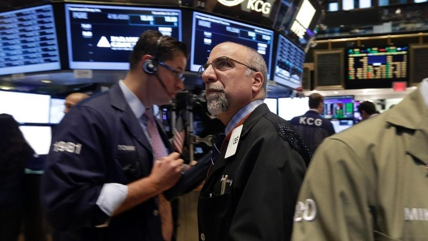 In this Monday, Nov. 24, 2014 photo, trader John Lotito, center, works on the floor of the New York Stock Exchange. U.S. stocks rose in early trading Tuesday, Nov. 25, after the government revised up its estimate for economic growth in the third quarter, giving the U.S. its strongest six months of growth in a decade. Stocks are trading at all-time highs. (AP Photo/Richard Drew)