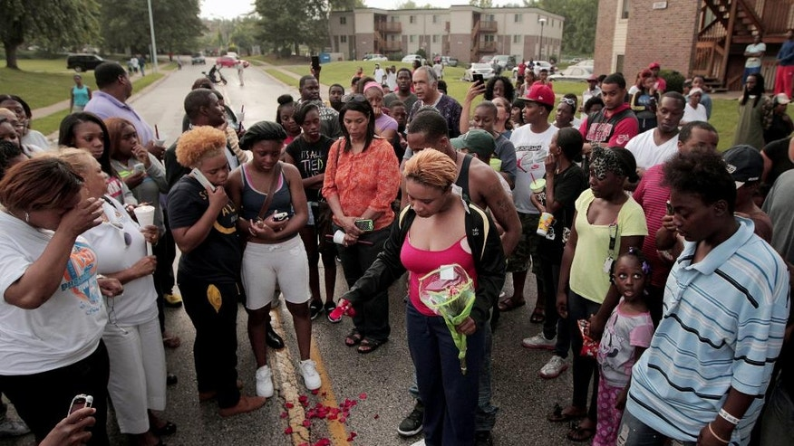 FILE- In this Aug. 9, 2014, file photo, Lesley McSpadden, center, drops rose petals on the blood stains from her 18-year-old son Michael Brown who was shot and killed a police officer in Ferguson, Mo., Aug. 9.  With a grand jury's decision this week not to indict police officer, Darren Wilson for Brown's killing, prosecutors released thousands of pages of testimony, interviews and documents that shine new and often harsh light on the events that unfolded in this suburb's darkest hours. (AP Photo/St. Louis Post-Dispatch, Huy Mach, File)