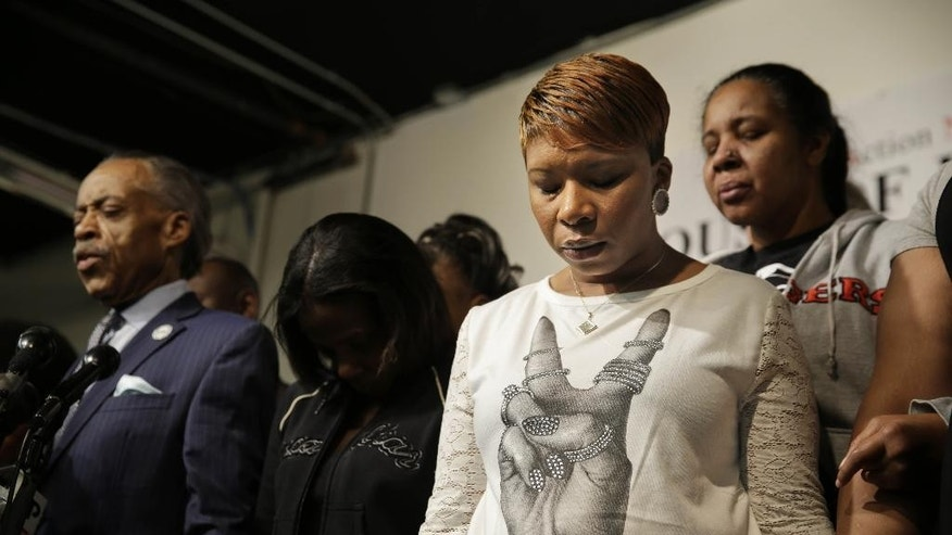 Lesley McSpadden, mother of Michael Brown, second from right, prays with other families and Al Sharpton, left, at the National Action Network headquarters in New York, Wednesday, Nov. 26, 2014. On the day before Thanksgiving, Sharpton brought together the families of Michael Brown, Eric Garner and Akai Gurley, all black men recently killed by police officers. (AP Photo/Seth Wenig)