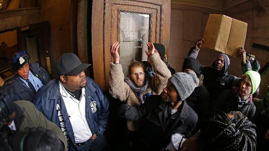 "Protesters confront law enforcement officers as they try to enter City Hall Wednesday, Nov. 26, 2014, in St. Louis. Several people protesting the Ferguson grand jury decision stormed into City Hall in St. Louis on Wednesday, leading police to lock down the building and to call in more than a hundred additional officers. At least two people were arrested after the incident, in which the protesters shouted ""Shame, shame"" while rushing into the building.  (AP Photo/Charlie Riedel)"