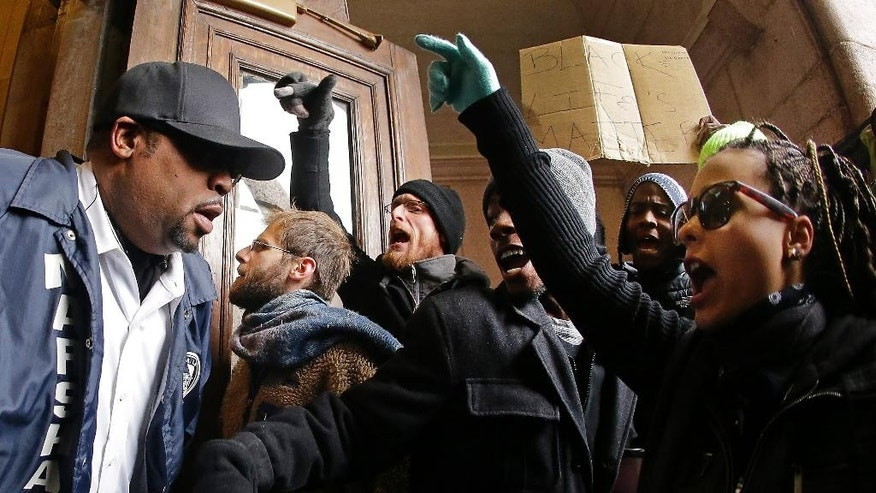 "Protesters confront a law enforcement officer as they try to enter City Hall Wednesday, Nov. 26, 2014, in St. Louis. Several people protesting the Ferguson grand jury decision stormed into City Hall in St. Louis on Wednesday, leading police to lock down the building and to call in more than a hundred additional officers. At least two people were arrested after the incident, in which the protesters shouted ""Shame, shame"" while rushing into the building.  (AP Photo/Charlie Riedel)"