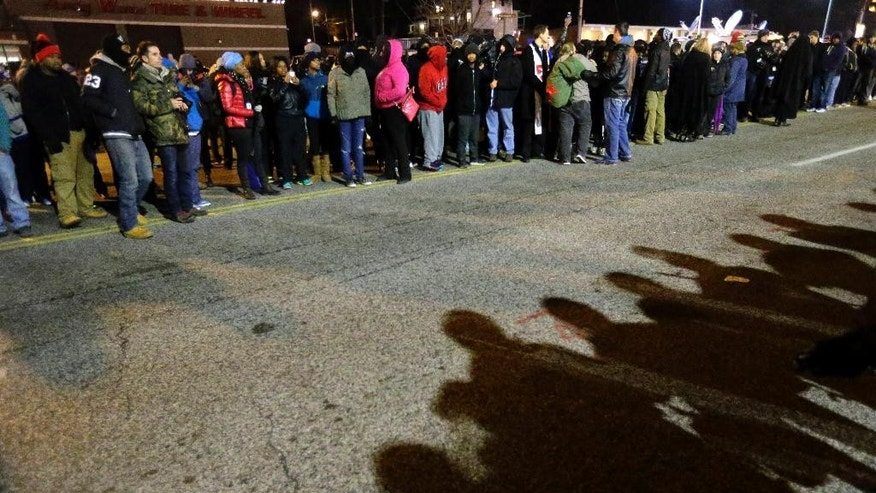 Protesters line up in front of the Ferguson Police Department on Tuesday, Nov. 25, 2014, in Ferguson, Mo. Missouri's governor ordered hundreds more state militia into Ferguson on Tuesday, after a night of protests and rioting over a grand jury's decision not to indict police officer Darren Wilson in the fatal shooting of Michael Brown, a case that has inflamed racial tensions in the U.S. (AP Photo/Charlie Riedel)