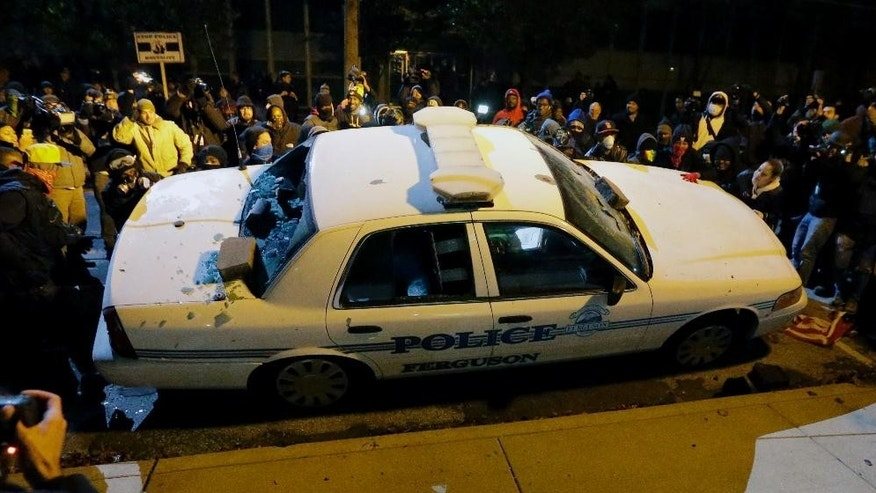 Protesters vandalize a police vehicle outside of the Ferguson city hall on Tuesday, Nov. 25, 2014, in Ferguson, Mo. Missouri's governor ordered hundreds more state militia into Ferguson on Tuesday, after a night of protests and rioting over a grand jury's decision not to indict police officer Darren Wilson in the fatal shooting of Michael Brown, a case that has inflamed racial tensions in the U.S. (AP Photo/Charlie Riedel)
