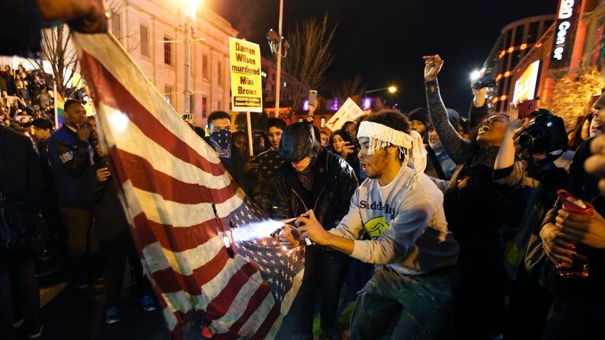 A protestor uses a lighter and an aerosol can to burn one of two American flags during a protest in the Chinatown area of Washington, Tuesday, Nov. 25, 2014. A grand jury in Ferguson, Mo., on Monday, Nov. 24th, 2014, declined to indict police officer Darren Wilson in the shooting death of Michael Brown, an unarmed African-American man. (AP Photo/Alex Brandon)