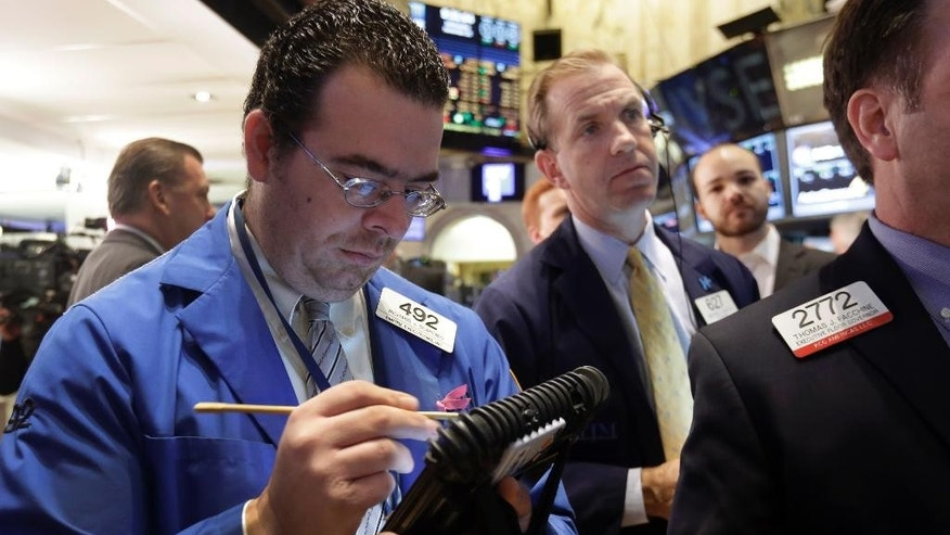 Traders Richard Scardino, left, and Michael Smyth work on the floor of the New York Stock Exchange, Wednesday, Nov. 26, 2014. Stock indexes are holding near record levels as traders digest some mixed news on the U.S. economy. (AP Photo/Richard Drew)