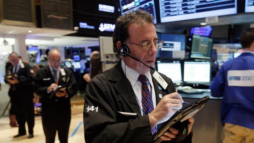 Trader Sal Suarino works on the floor of the New York Stock Exchange, Wednesday, Nov. 26, 2014. Stock indexes are holding near record levels as traders digest some mixed news on the U.S. economy. (AP Photo/Richard Drew)
