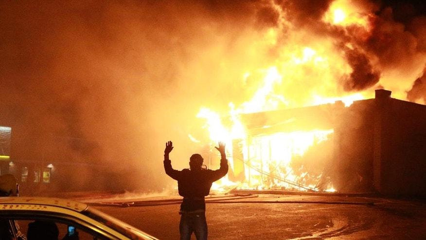 "FILE- In this Nov. 24, 2014 photo, a protestor poses for a ""hands up"" photo in front of a burning building on West Florissant Ave. in Ferguson, Mo. 'Hands Up, Don't Shoot' has become a rallying cry despite questions whether Michael Brown's hands were raised in surrender before being fatally shot by a Ferguson police officer. (AP Photo/St. Louis Post-Dispatch, Christian Gooden, File)"