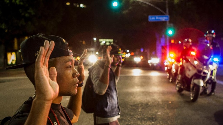 FILE- In this Nov. 26, 2014 photo, protesters kneel down with their hands up in front of Los Angeles police officers in downtown Los Angeles. 'Hands Up, Don't Shoot' has become a rallying cry despite questions whether Michael Brown's hands were raised in surrender before being fatally shot by a Ferguson police officer. (AP Photo/Damian Dovarganes, File)