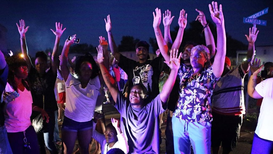 FILE- In this Aug. 9, 2014, file photo, a crowd gathers near the scene where 18-year-old Michael Brown was fatally shot by police in Ferguson, Mo. 'Hands Up, Don't Shoot' has become a rallying cry despite questions whether Michael Brown's hands were raised in surrender before being fatally shot by a Ferguson police officer. (AP Photo/St. Louis Post-Dispatch, David Carson, File)