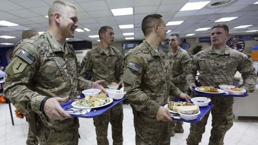 Nov. 27, 2014: NATO soldiers carry their Thanksgiving Day meals at the ISAF headquarters in Kabul, Afghanistan. This is the last Thanksgiving cerebration before the U.S. and NATO combat mission ends on Dec. 31 this year.