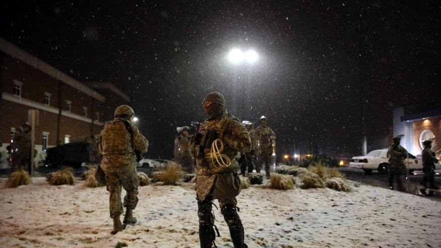 Snow falls as Missouri National Guard stand outside of the Ferguson Police Department Wednesday, Nov. 26, 2014, in Ferguson, Mo. A grand jury's decision not to indict Ferguson police officer , Darren Wilson, in the shooting death of Michael Brown has sparked protests nationwide, triggering debates over the relations between black communities and law enforcement. (AP Photo/Jeff Roberson)