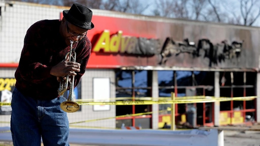 Eugene Gillis plays Christmas carols on his trumpet Friday, Nov. 28, 2014, along a section of West Florissant Avenue that saw heavy damage on Monday in Ferguson, Mo. The section of road has been closed, but reopened Friday, after many business were damaged after a grand jury decided not to indict a Ferguson police officer in the shooting death of Michael Brown. (AP Photo/Jeff Roberson)