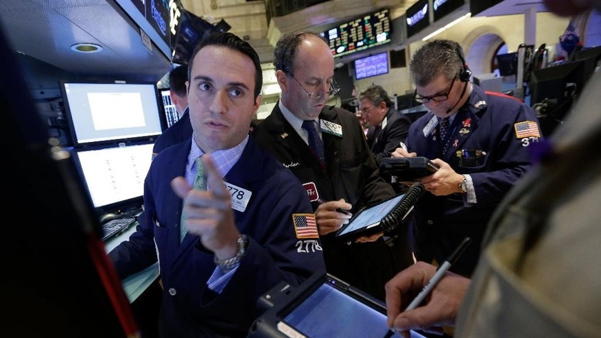 Specialist Michael Gagliano, left, who handles energy stocks, works with traders on the floor of the New York Stock Exchange, Friday, Nov. 28, 2014. U.S. stocks indexes were mixed in early trading, as tumbling oil prices weighed on shares of Exxon Mobil, Chevron and other oil and gas giants. Airlines, however, made gains. (AP Photo/Richard Drew)