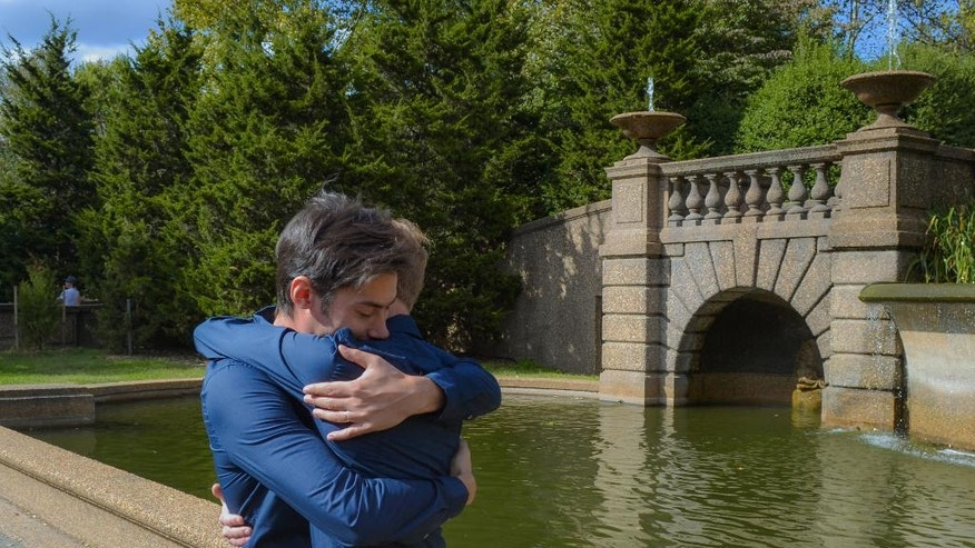In this Oct. 18, 2014, photo provided by Michael Knaapen, Andrew Nasonov hugs Igor Bazilevsky, left, after the couple was married at Meridian Hill Park in Washington. They both came to the U.S. from Russia in July, and are preparing to file an application seeking asylum in the U.S. The increase in the overall applications for asylum by Russians is due in part to the worsening anti-gay climate in Russia, according to Immigration Equality, a New York-based organization which provides legal services for lesbian, gay, bisexual and transgender immigrants. (AP Photo/Michael Knaapen)