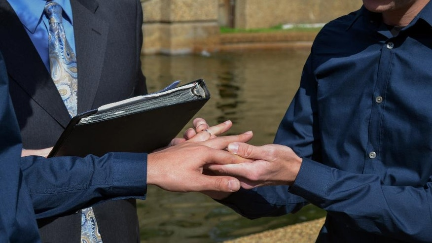 In this Oct. 18, 2014, photo provided by Michael Knaapen, Andrew Nasonov, right, exchanges rings with Igor Bazilevsky during their marriage ceremony at Meridian Hill Park in Washington. The couple both came to the U.S. from Russia in July, and are preparing to file an application seeking asylum in the U.S.(AP Photo/Michael Knaapen)