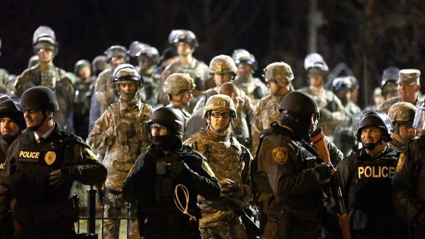 Police and Missouri National Guardsmen stand guard as protesters gather in front of Ferguson Police Department on Friday, Nov. 28, 2014, in Ferguson, Mo. Several protesters have been taken into custody during a demonstration outside the police department. Tensions escalated late Friday during an initially calm demonstration after police said protesters were illegally blocking West Florissant Avenue. (AP Photo/Jeff Roberson)