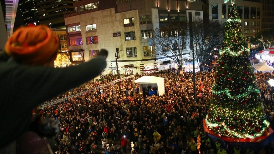 A protester looks out over a sea of people at Westlake Center where Ferguson protesters disrupted the annual tree lighting, Friday, Nov.28, 2014, in Seattle. The tree was still lit but the mall closed after a few hundred protesters forced their way onto the upper level stage where carolers and other performers were to perform. (AP Photo/seattlepi.com, Joshua Trujillo)
