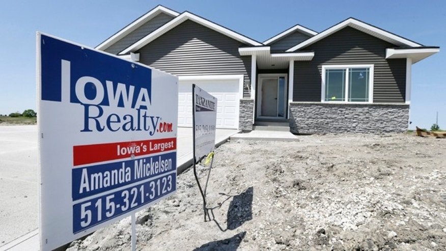 FILE: A sign sits in front of a new home for sale in West Des Moines, Iowa.
