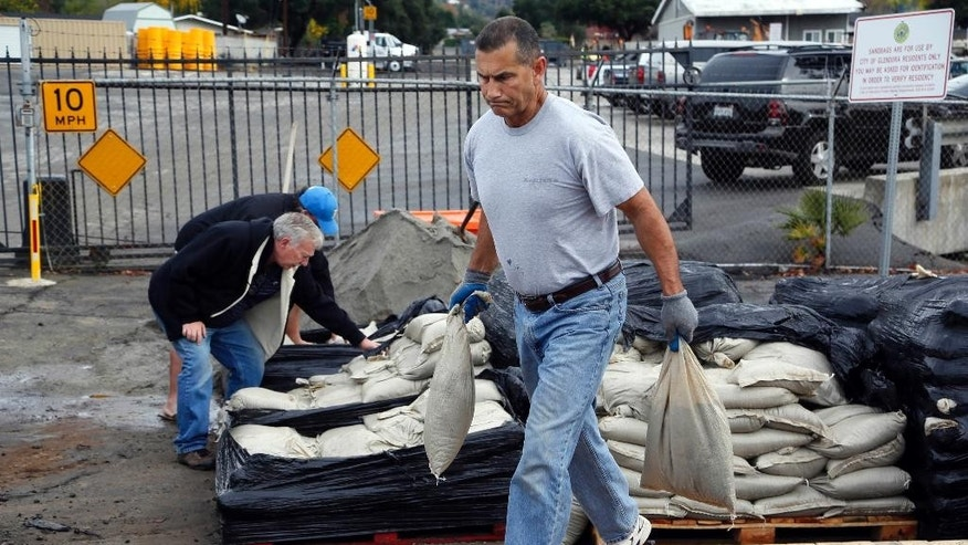 Denis Carruth collects sand bags to protect his home from possible flooding in Glendora, Calif. on Monday, Dec.1, 2014.  California is bracing for the arrival of a new, more powerful Pacific storm following a weekend of scattered rain, showers and snow. The National Weather Service says a low-pressure system off the coast will draw a plume of subtropical moisture northward into the state beginning on Tuesday. (AP Photo/Nick Ut)