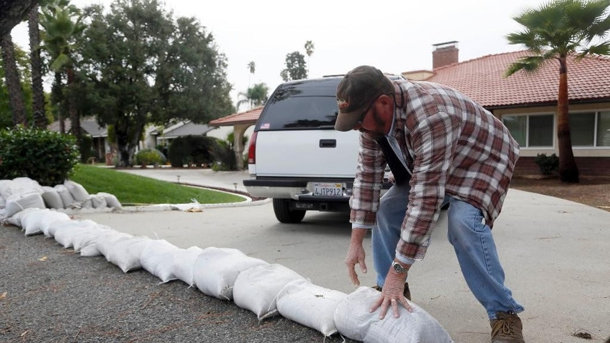 Richard Pope places sand bags along his driveway to protect his home from an expected storm in Glendora, Calif. on Monday, Dec.1, 2014.  California is bracing for the arrival of a new, more powerful Pacific storm following a weekend of scattered rain, showers and snow. The National Weather Service says a low-pressure system off the coast will draw a plume of subtropical moisture northward into the state beginning on Tuesday. (AP Photo/Nick Ut)