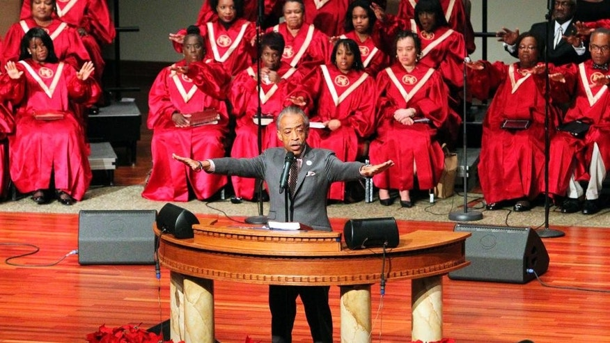Rev. Al Sharpton preaches to a crowd on Sunday, Nov. 30, 2014, at Friendly Temple Missionary Baptist Church in St. Louis. Family members of 18-year-old Michael Brown, who was shot and killed by a white Ferguson, Mo., police officer, attended the church service where the civil rights activist preached. (AP Photo/St. Louis Post-Dispatch, J.B. Forbes)