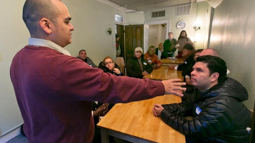 Educator Pedro Garcia, left, talks with immigrants during Shared Journeys, a workshop in English for Speakers of Other Languages, or ESOL, run by the Tenement Museum, on New York's Lower East Side, Friday, Nov. 21, 2014. Held in a restored 4-story tenement building that housed 7,000 working class immigrants between 1863 and 1935, the program invites them to learn about immigrants of the past by visiting the restored tenement apartments and then sharing and talking about their own experiences. (AP Photo/Richard Drew)