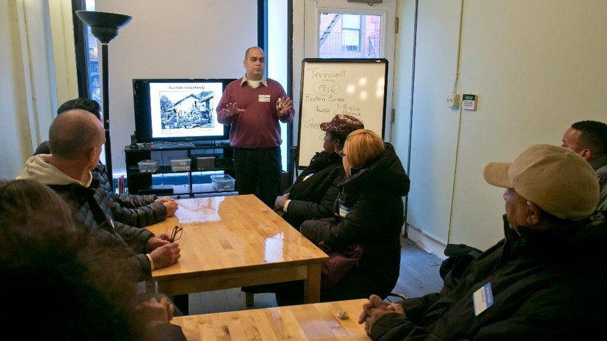 Educator Pedro Garcia, center, talks with immigrants during Shared Journeys, a workshop in English for Speakers of Other Languages, or ESOL, run by the Tenement Museum, on New York's Lower East Side, Friday, Nov. 21, 2014. Held in a restored 4-story tenement building that housed 7,000 working class immigrants between 1863 and 1935, the program invites them to learn about immigrants of the past by visiting the restored tenement apartments and then sharing and talking about their own experiences. (AP Photo/Richard Drew)