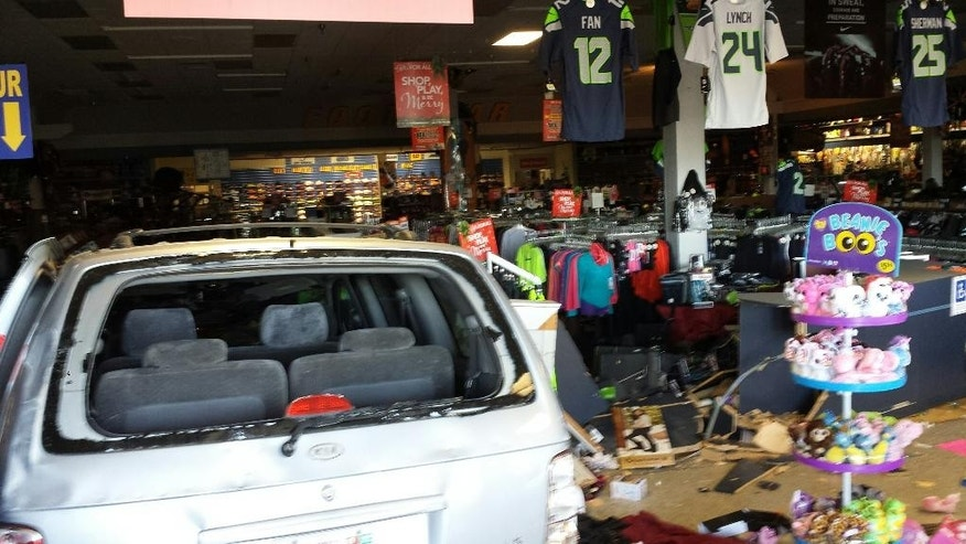This photo provided by the King County Sheriff's Office shows a car which crashed through the locked doors of a sporting goods store in Burien, Wash. on Tuesday, Dec. 2, 2014. Sheriff's deputies took one person into custody after the crash, which officials said appeared to be a burglary attempt targeting the store's firearms. (AP Photo/King County Sherriff's Office)