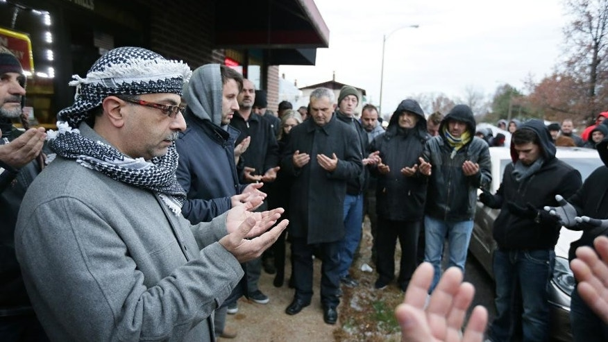 Zuhdi Masri, left, prays for murder victim Zemir Begic with a group of other Bosnians gathered on Holly Hills Avenue in St. Louis on Monday, Dec. 1, 2014. After the prayer, police blocked traffic as hundreds of people marched from Holly Hills Avenue down Gravois Road to Itaska Street where Begic was killed early Sunday, Nov. 30, 2014. Police in St. Louis say they've arrested two juveniles and are looking for two other suspects in the killing of a Begic, a Florida man who was beaten to death with hammers. (AP Photo/St. Louis Post-Dispatch, David Carson)  EDWARDSVILLE INTELLIGENCER OUT; THE ALTON TELEGRAPH OUT