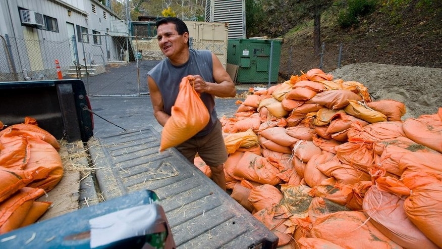 In this Monday, Dec. 1, 2014 photo, Silverado Canyon resident Eddie Armas loads sandbags into his truck to build a mudslide barrier ahead of the expected rain on Tuesday, in Silverado Canyon, Calif. (AP Photo/The Orange County Register, Sam Gangwer)