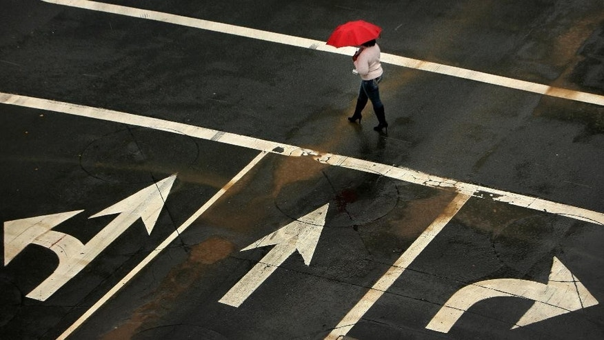 A women, prepared with an umbrella, crosses an intersection in downtown Riverside, Calif., as light rain falls on Tuesday, Dec. 2 2014. (AP Photo/The Press-Enterprise, Stan Lim)  MAGS OUT; MANDATORY CREDIT