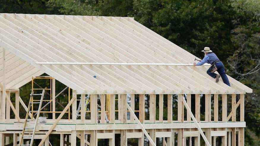 FILE - In this Oct. 9, 2014 file photo, a man works on the roof of a building under construction in Middlefield, Ohio. The Commerce Department reports on U.S. construction spending in October on Tuesday, Dec. 2, 2014. (AP Photo/Tony Dejak, File)