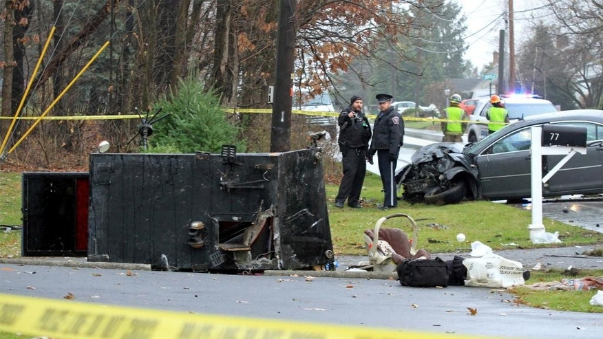 Police stand at the scene where a horse-drawn buggy, foreground, was hit when a car, right, crashed into it head-on in Lancaster, Pennsylvania injuring four people in the buggy and one person in the automobile Wednesday, Dec. 3, 2014. The accident on Route 896 is the latest significant crash involving an Amish buggy in Pennsylvania this year. (AP Photo/LNP Media Group, Casey Kreider)