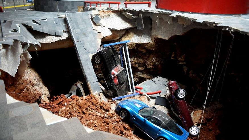 FILE - In this Feb. 12, 2014 file photo is a sinkhole that opened up swallowing eight classic and historic Corvettes at the National Corvette Museum in Bowling Green, Ky. A 1992 Corvette convertible, the 1,000,000th built by Chevrolet and one of eight pulled from the sinkhole, will undergo restoration by General Motors' Design Center Fabrication Operations in January and will take at least six months to complete. (AP Photo/Michael Noble Jr., File)