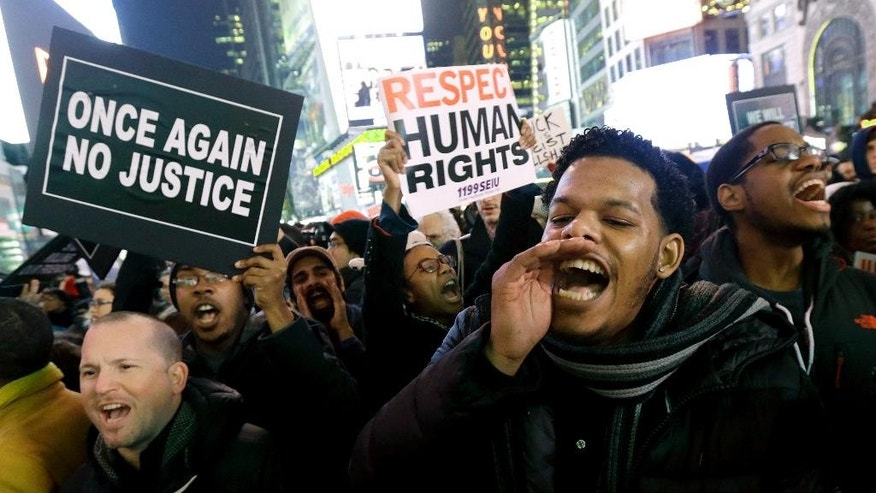 Protestors shout at Times Square after it was announced that the New York City police officer involved in the death of Eric Garner is not being indicted, Wednesday, Dec. 3, 2014, in New York. A grand jury cleared the white New York City police officer Wednesday in the videotaped chokehold death of Garner, an unarmed black man, who had been stopped on suspicion of selling loose, untaxed cigarettes, a lawyer for the victim's family said. A video shot by an onlooker and widely viewed on the Internet showed the 43-year-old Garner telling a group of police officers to leave him alone as they tried to arrest him. The city medical examiner ruled Garner's death a homicide and found that a chokehold contributed to it. (AP Photo/Julio Cortez)