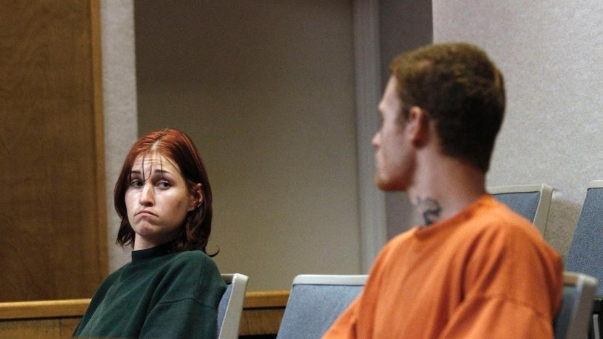 "FILE - In this Oct. 11, 2011 file photo, Holly Grigsby, left, looks at her boyfriend, David ""Joey""  Pedersen, during an appearance in Yuba County Superior Court in Marysville, Calif.  An Oregon State Police detective, David Steele, who investigated the 2011 Northwest killing spree by the pair of white supremacists is expected to plead guilty to charges of forgery and official misconduct related to the case, a prosecutor said today.  Steele will enter the plea Friday, Dec. 5, 2014 at his arraignment in Salem, Ore., and be sentenced according to officials. (AP Photo/Rich Pedroncelli, File)"